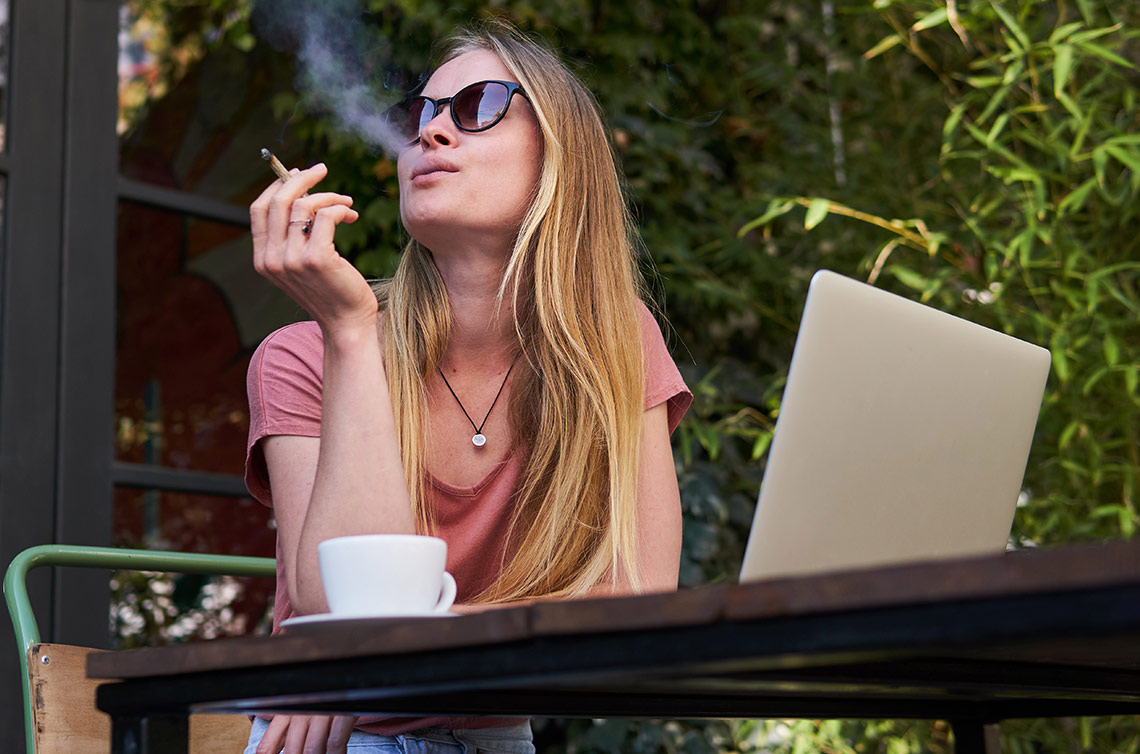 Beautiful sophisticated girl with sun glasses smoking weed-cannabis