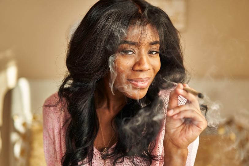 How-Long-Does-A-Marijuana-High-Last-african american woman smoking pre-roll marijuana joint